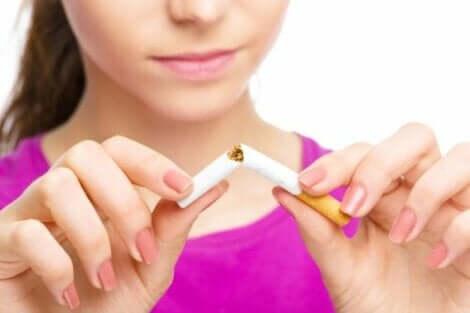 Een vrouw die een sigaret in 2 stukken breekt
