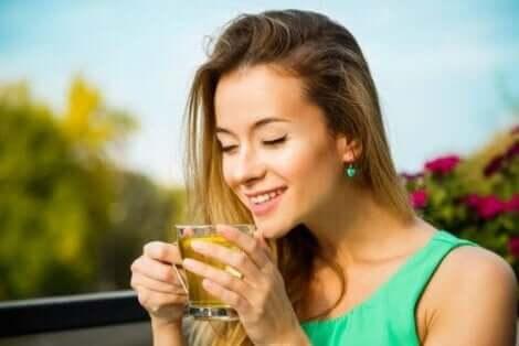 Een vrouw die lacht en thee drinkt