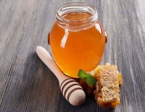 Een pot honing met een stukje honingraat ernaast