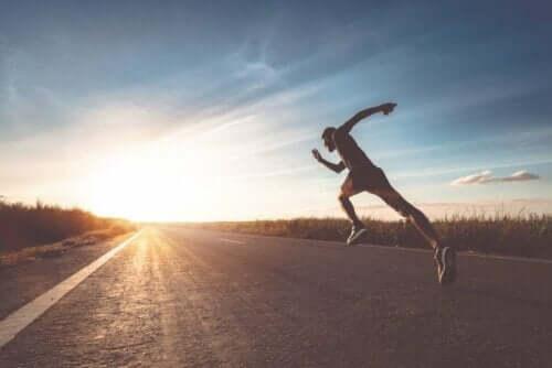 Een man loopt hard op een verharde weg