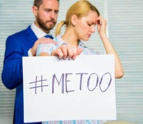 Een vrouw houdt een bord met de hashtag me too omhoog