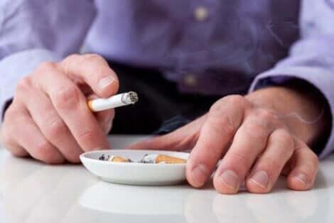 Een man houdt een sigaret vast boven een asbak