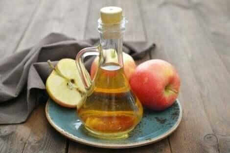 Appelazijn in een fles en verse appels op een bord