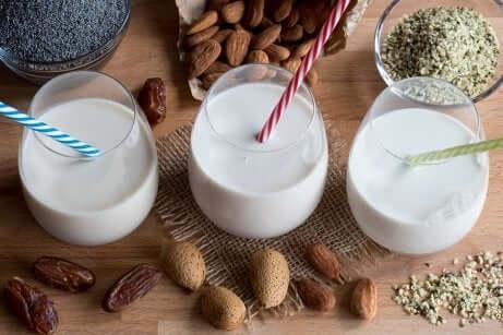 Drie glazen amandelmelk met noten eromheen