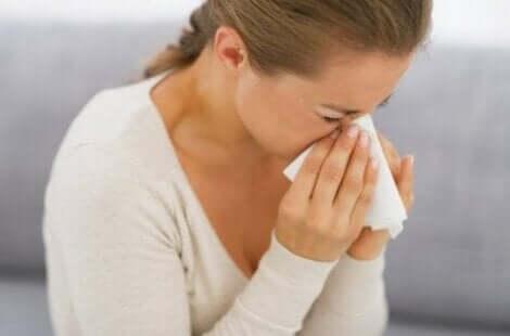 Een vrouw niest door een allergie voor huismijt