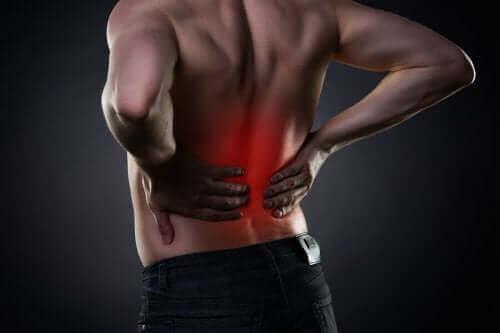 Man houdt zijn pijnlijke rug vast