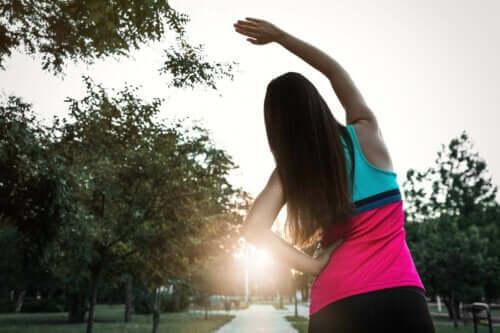 Een vrouw doet strekoefeningen in een park