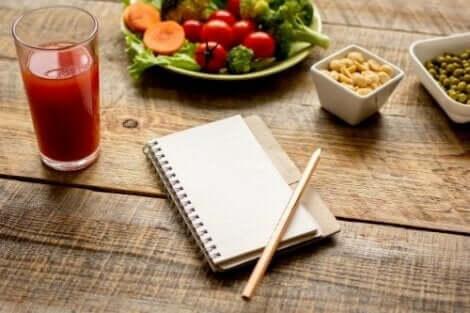Een glas tomatensap met een gezonde salade en een opschrijfboekje op tafel