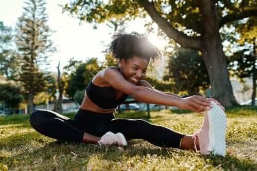 Een vrouw doet strekoefeningen op een grasveld