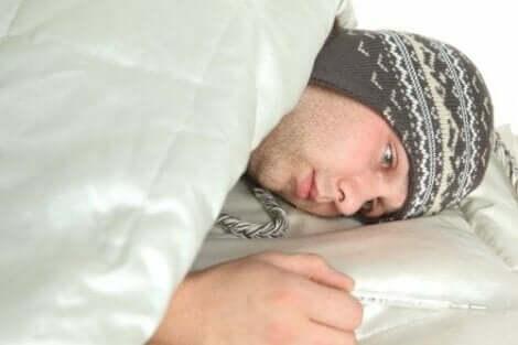 Een man ligt ziek in bed met een muts op