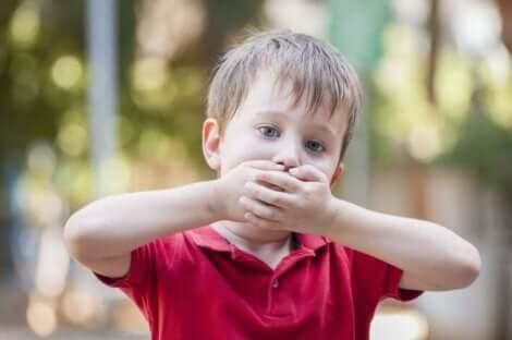Een kind dat zijn mond met beide handen bedekt