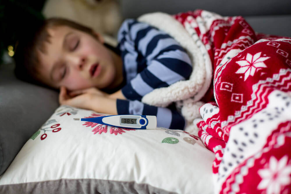 Kind ligt met koorts op de bank