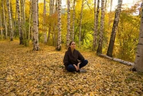 Vrouw zit in het bos op de grond