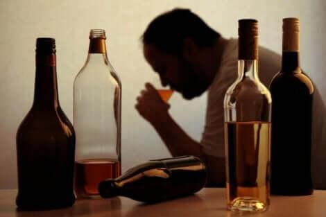 Een man drinkt een glas bier met flessen op tafel