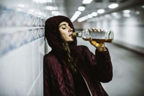 Een vrouw brengt een fles aan haar mond in een tunnel