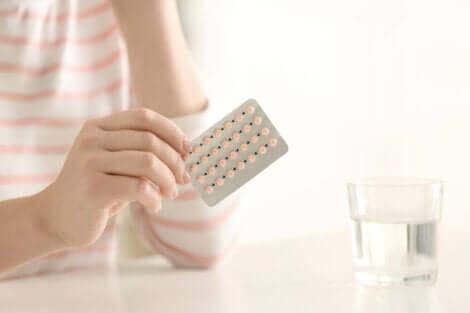 Een vrouw met een strip pillen in haar hand