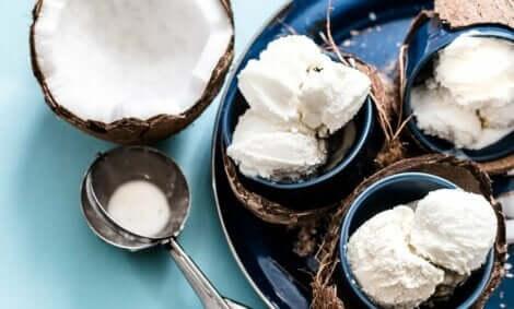 Een halve kokosnoot naast schaaltjes met ijs