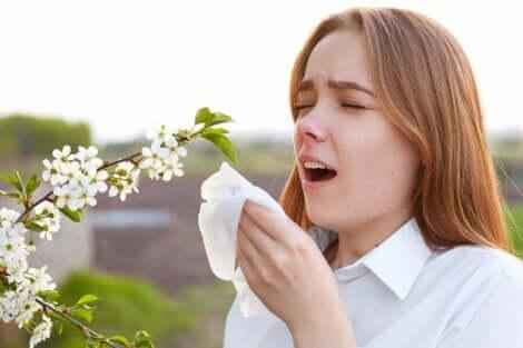 Een vrouw staat naast een plant en niest