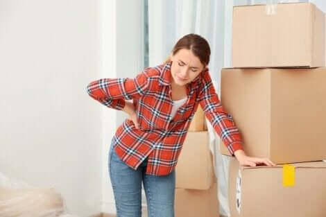 Een vrouw leunt tegen een stapel dozen met haar hand tegen haar rug