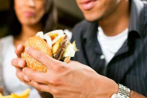 Een man eet een dubbele hamburger