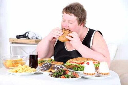 Man die aan een tafel vol eten zit te schransen