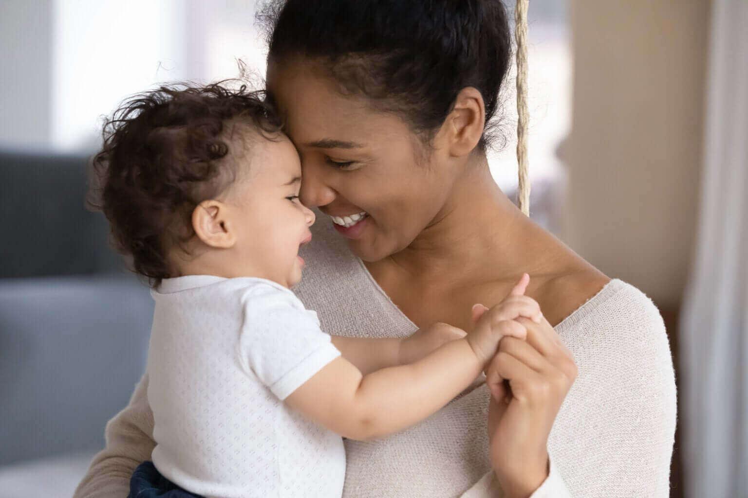 Baby is blij in de armen van mama