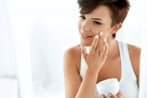 Een vrouw smeert crème op haar gezicht