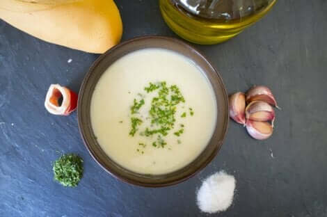 Een kom romige soep met uien, bacon en specerijen ernaast