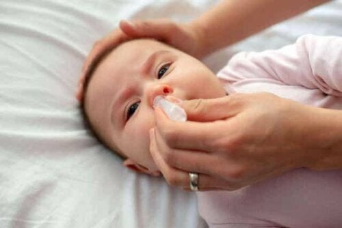 Een baby die een neusspoeling krijgt