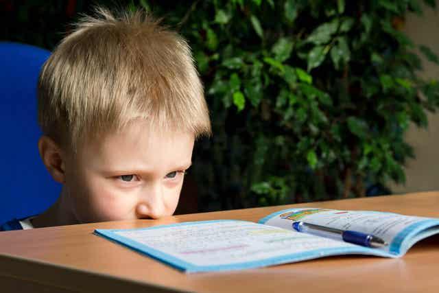 Jongen kijkt tegen zijn schoolwerk op