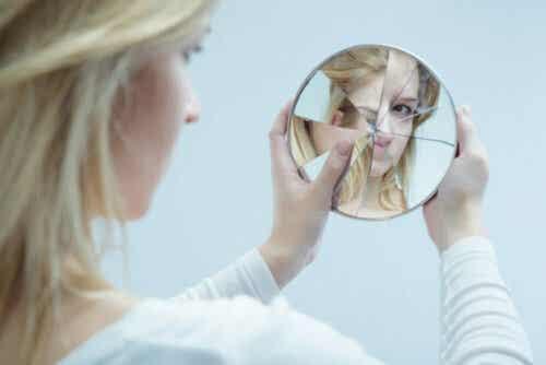 Vrouw kijkt in een kapotte spiegel