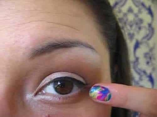 Vrouw wijst naar gezwollen ooglid