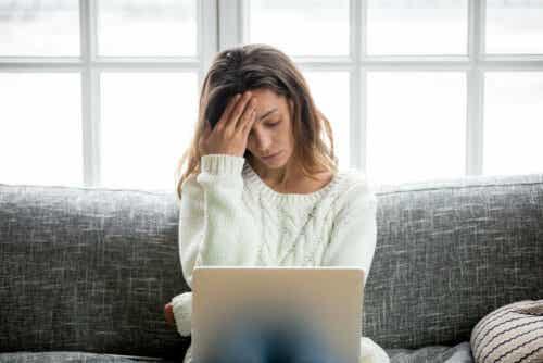 Een vrouw met haar hand tegen haar hoofd zit achter een laptop