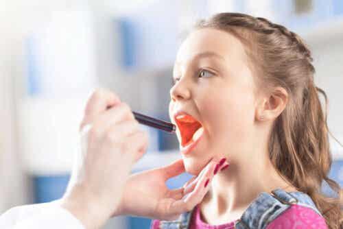De arts onderzoekt de keel om faryngotonsillitis te diagnosticeren