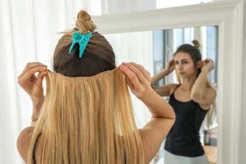 Een vrouw doet haarextensies in haar haar