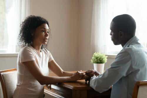 Twee mensen praten, terwijl ze elkaars handen vasthouden