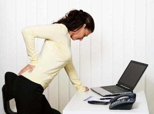 Een vrouw houdt haar hand tegen haar onderrug