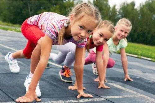 Drie jonge meisjes maken zich klaar voor een hardloopwedstrijdje