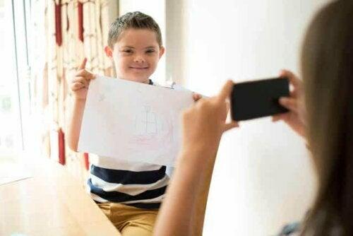 Een jongen met het syndroom van Down houdt zijn tekening omhoog