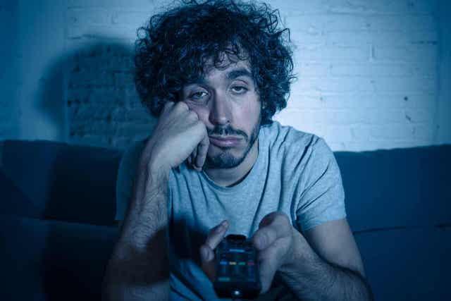 Een man die zich verveelt terwijl hij in het donker tv kijkt