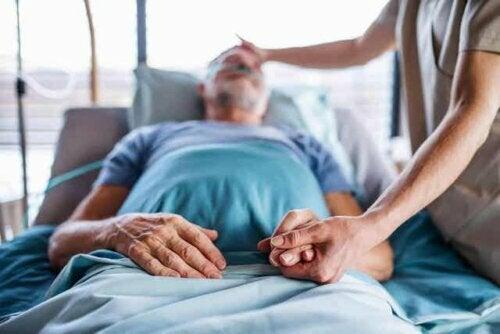 Een verpleegster die voor een bedlegerige patiënt zorgt