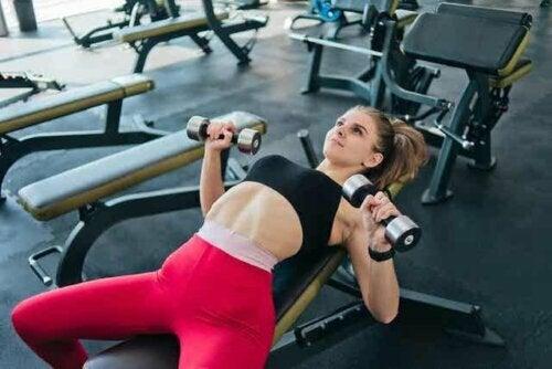 Een vrouw die gewichten heft in de sportschool