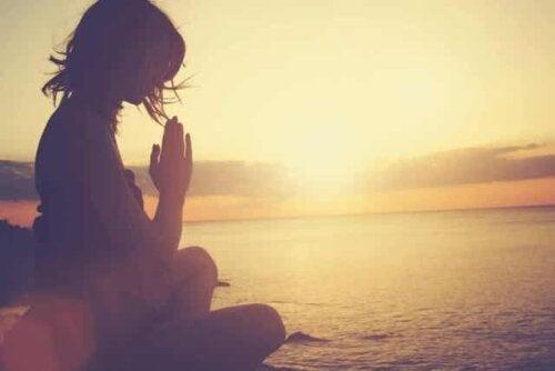 Een vrouw mediteert op het strand bij zonsondergang