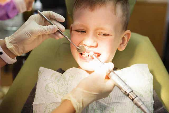Orthodontist bekijkt het gebit van een kind