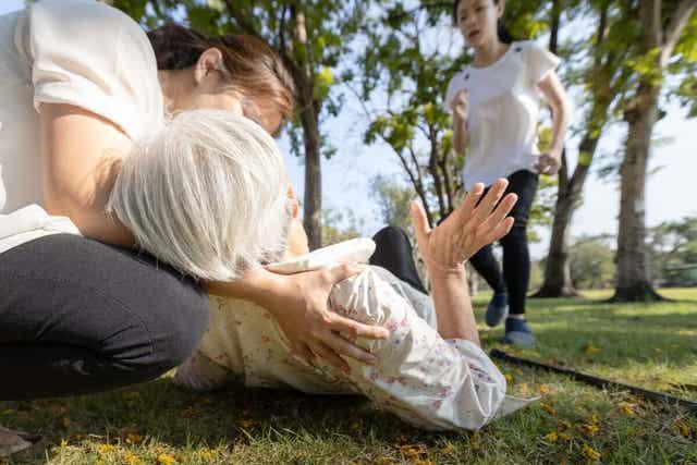Oudere vrouw ligt buiten op de grond