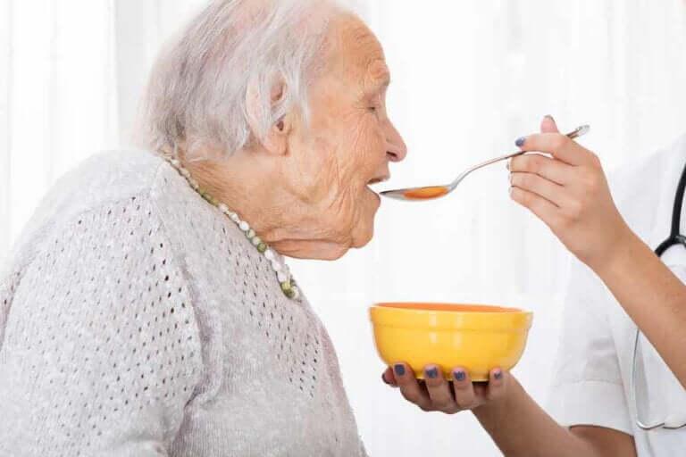 Oudere vrouw eet vloeibaar voedsel