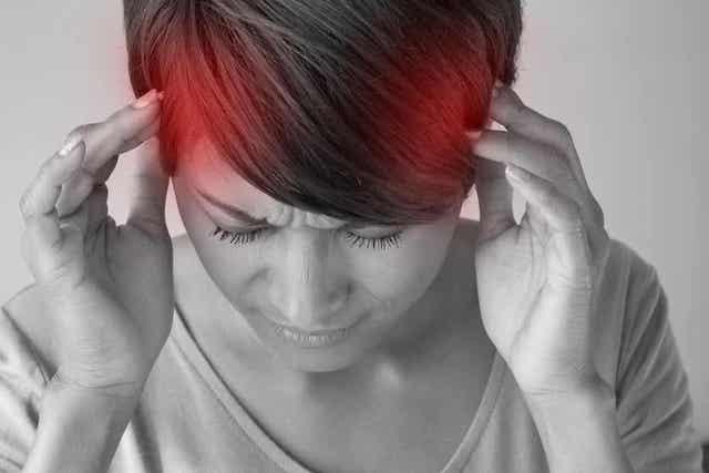 Vrouw houdt haar pijnlijke hoofd vast