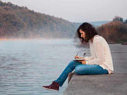 Vrouw zit bij het water te schrijven