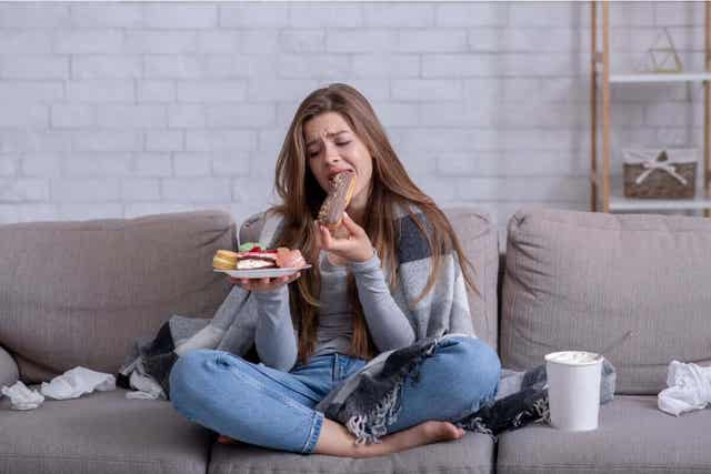 Vrouw met een bord ongezonde snacks
