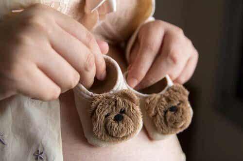 Een vrouw houdt twee kleine babyschoenen in haar handen